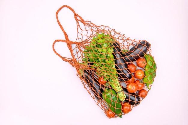 Torba na zakupy wielokrotnego użytku z eko warzywami na różowym tle. zero odpadów, bez plastiku.