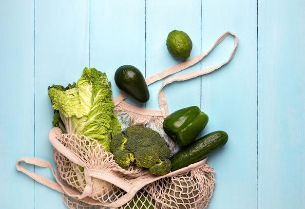 Torba na zakupy z zielonymi produktami na turkusowym tle
