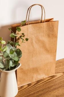 Torba papierowa i roślina na drewnianej powierzchni