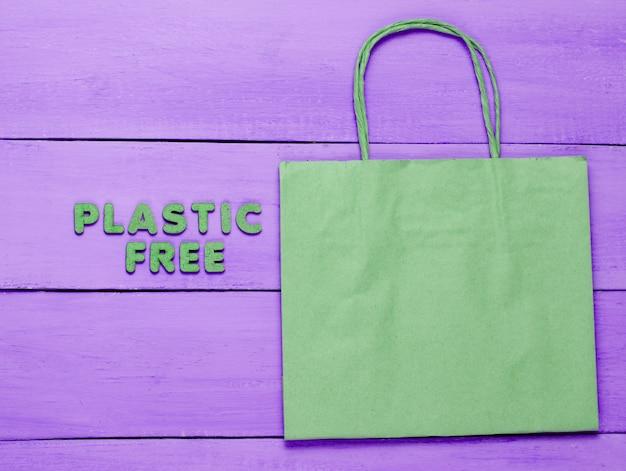 Torba papierowa na fioletowym drewnianym pudełku z napisem plastik gratis
