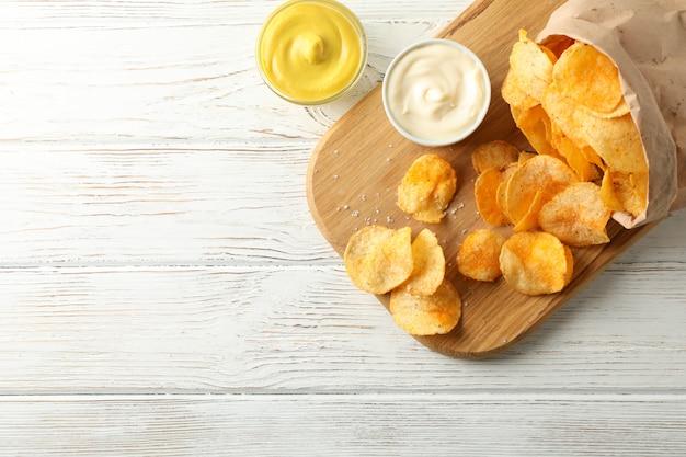 Torba papierowa z chipsami ziemniaczanymi. przekąski do piwa, sos na desce do krojenia, na białym drewnie, miejsce na tekst. widok z góry