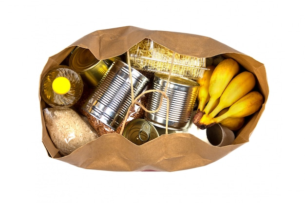 Torba papierowa z kryzysowym zaopatrzeniem w żywność na okres izolacji kwarantanny na różowym tle, makaron, gryka, konserwy, ryż, banany na białym tle na białym tle