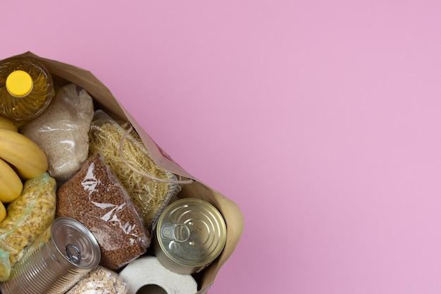 Torba papierowa z kryzysowym zaopatrzeniem w żywność na okres izolacji kwarantanny na różowym tle