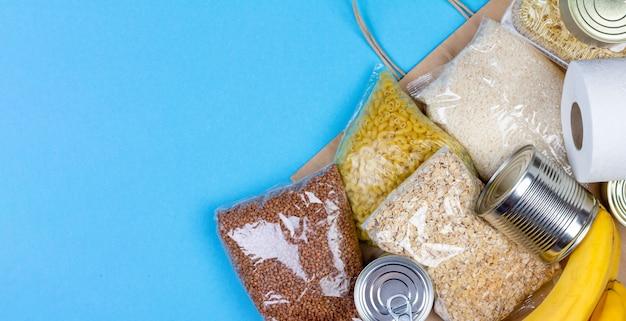 Torba papierowa z kryzysowym zaopatrzeniem w żywność na okres kwarantanny izolacji koronawirusa, ryżu, makaronu, płatków owsianych, żywności w puszkach, papieru toaletowego, gryki, bananów na niebieskim tle