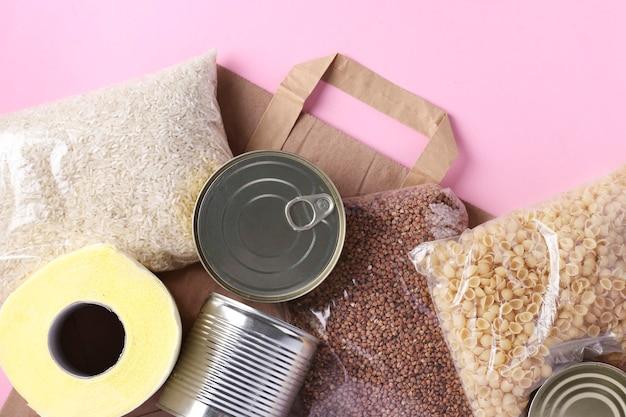 Torba papierowa z zapasami żywności kryzysowej na okres kwarantanny na różowej powierzchni. ryż, kasza gryczana, makaron, konserwy, papier toaletowy. dostawa żywności, darowizny, widok z góry, zbliżenie