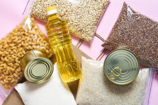 Torba papierowa z żywnością dostarcza zapasów żywności kryzysowej do kwarantanny. makaron, kasza gryczana, cukier, ryż, zboża, konserwy. darowizna. widok z góry