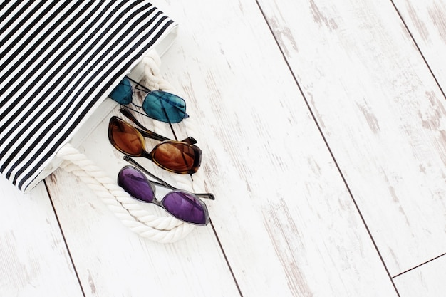 Torba plażowa i okulary przeciwsłoneczne na starym malowanym drewnianym tle