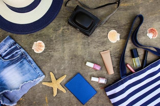 Torba plażowa, kapelusz przeciwsłoneczny, kosmetyki, spodenki jeansowe, aparat, muszle na starym drewnianym tle.
