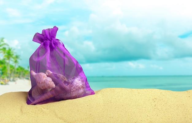 Torba seashells na piasku przy plażą
