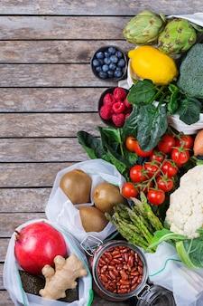 Torba tekstylna z siateczki z produktami, owocami i warzywami. zero odpadów, przyjazny dla środowiska, bez plastiku, recyklingowany, wielokrotnego użytku, zrównoważony pomysł na zakupy spożywcze. kopiuj przestrzeń, płaskie tło świecące