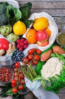 Torba tekstylna z siateczki z produktami, owocami i warzywami. zero odpadów, przyjazny dla środowiska, bez plastiku, recyklingowany, wielokrotnego użytku, zrównoważony pomysł na zakupy spożywcze. płaskie tło świeckich