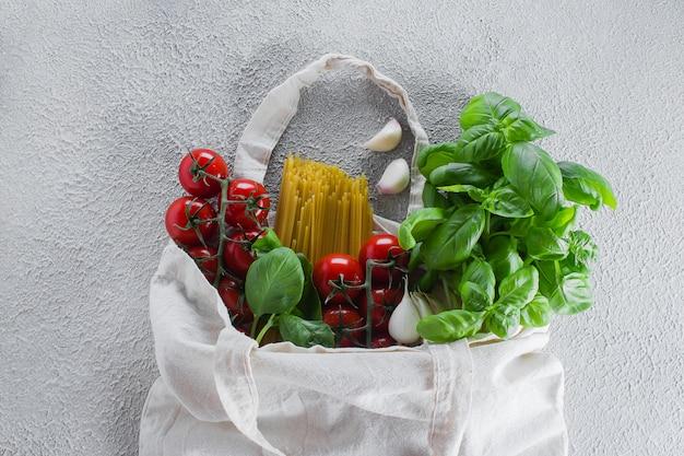 Torba wielokrotnego użytku z artykułami spożywczymi. torba z grubego materiału, minimalna ilość odpadów. bazylia, pomidory cherry, czosnek w woreczku z tkaniny