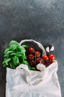 Torba wielokrotnego użytku z artykułami spożywczymi. torba z grubego materiału, minimalna ilość odpadów. świeża bazylia, pomidory cherry, czosnek w woreczku z tkaniny