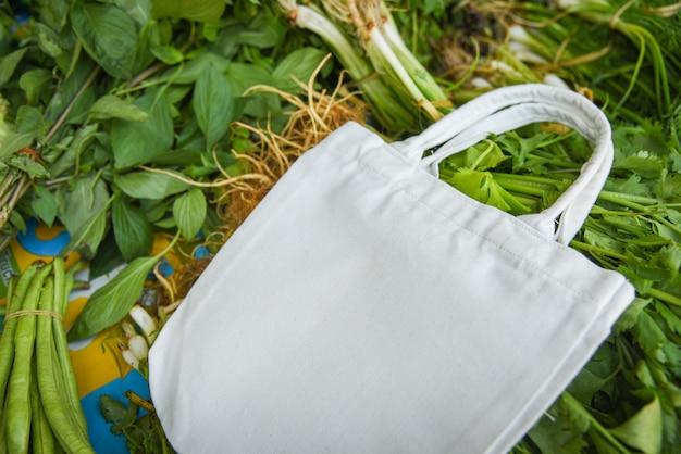 Torba z ekologicznej tkaniny bawełnianej na świeżych warzywach na wolnym rynku na zakupy z tworzyw sztucznych / zero odpadów zużywa mniej plastiku