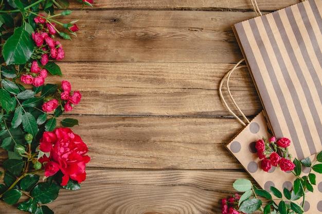 Torby do pakowania z uchwytami w kropki i paski i naturalne czerwone róże na drewnianym tle. leżał z copyspace