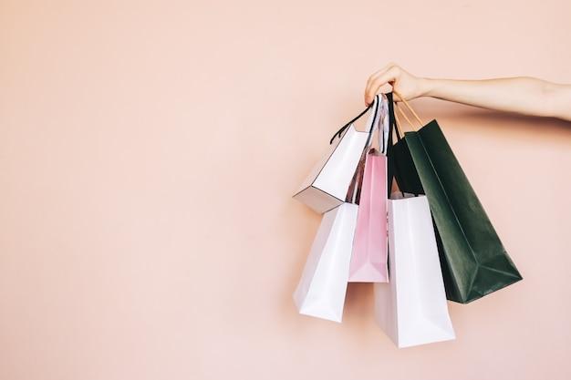 Torby na zakupy w rękach na białym tle na beżowym tle pastelowych. koncepcja zakupów.