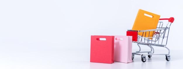 Torby na zakupy w srebrnym czerwonym koszyku na białym tle na białym tle tabeli, koncepcja pozostania porządkiem w domu, bliska, skopiuj projekt przestrzeni.