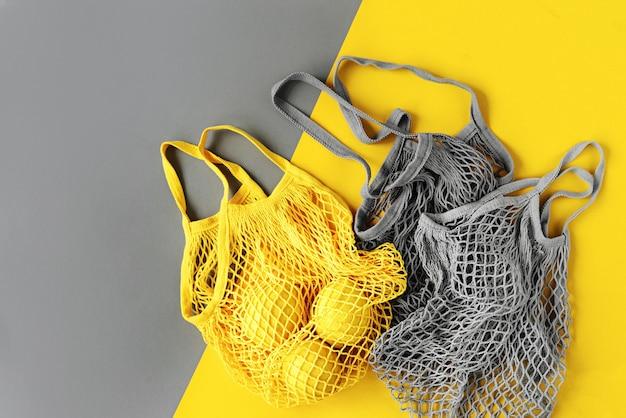 Torby na zakupy wielokrotnego użytku z cytrynami. kolory roku 2021 ultimate grey i illuminating. paleta trendów kolorystycznych. stylowe tło