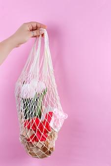 Torby na zakupy wielokrotnego użytku z papierowymi pudełkami prezentowymi i świeżymi wiosennymi tulipanami w ręce kobiety na różowym tle.