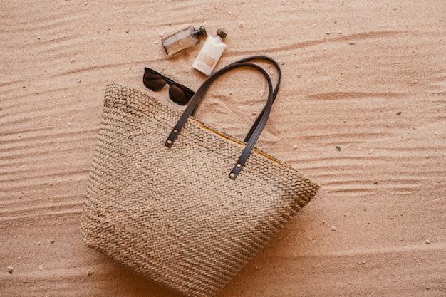 Torebka damska obok perfum i okularów przeciwsłonecznych postawiona na piasku