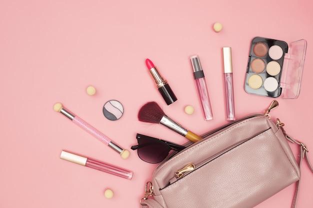Torebka damska z kosmetykami, narzędziami do makijażu i akcesoriami na różowym tle, uroda, moda, koncepcja zakupów, płaski układ. wysokiej jakości zdjęcie