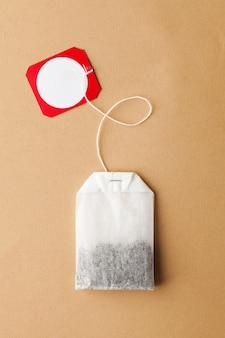 Torebka na herbatę z pustym tagiem na logo i miejscem na tekst na brązowym tle w stylu minimalizmu. układ dla herbaciarni.