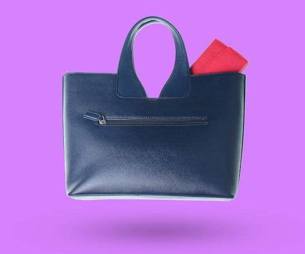 Torebka w skórzanej torbie na białym tle na fioletowym tle