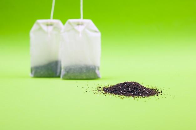 Torebki herbaciane o smaku cytryny na zielonym stole.