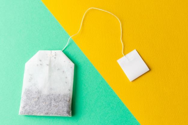 Torebki herbaciane z białymi etykietami na pastelowym zielonym i jasnożółtym tle