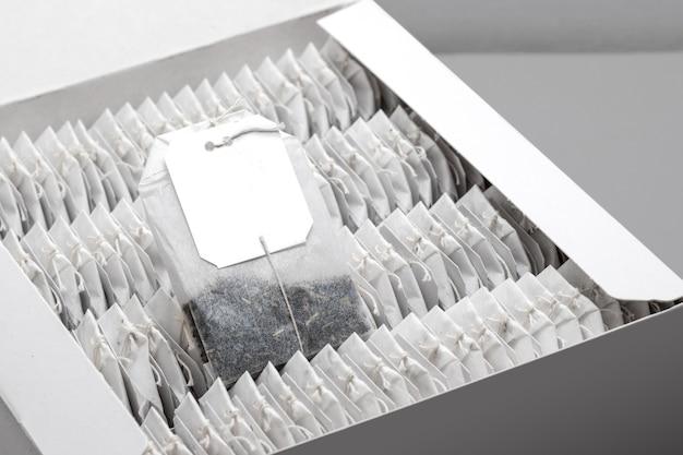 Torebki herbaty w pudełku kartonowym ustawione z bliska. pusty szablon makiety do brandingu produktu