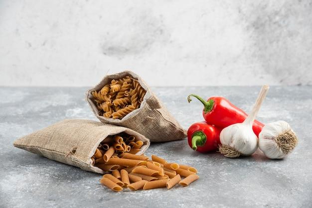 Torebki makaronowe z czerwoną papryczką chili i ząbkami czosnku na marmurze.