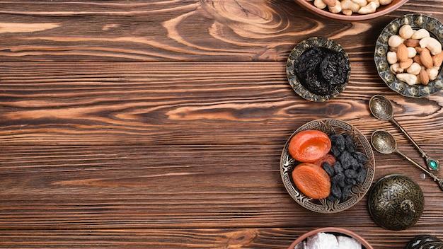 Toreutic grawerowane artystyczne metalowe miski z suszonymi owocami i orzechami na drewnianej powierzchni