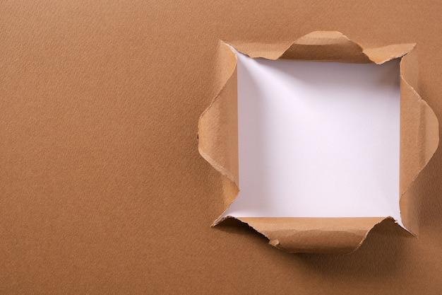 Torn brązowego papieru kwadratowej dziury tła biała rama