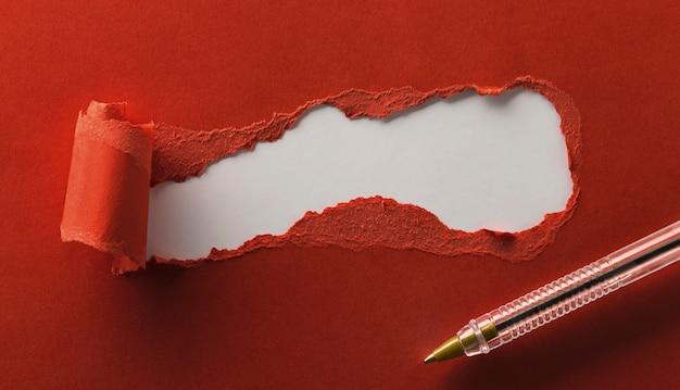 Torn czerwony papier z miejsca na tekst i długopis z bliska