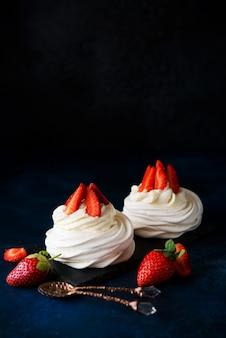 Tort anna pavlova ze śmietaną i świeżymi truskawkami na ciemnym tle, miejsce na kopię