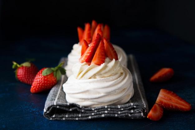 Tort anna pavlova ze śmietaną i świeżymi truskawkami na ciemnym tle, z bliska