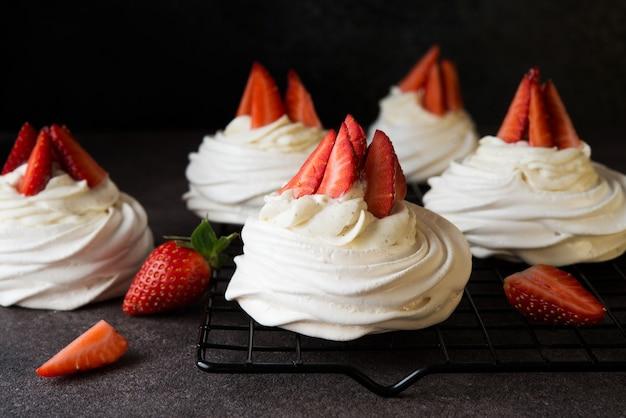 Tort anna pavlova ze śmietaną i świeżymi truskawkami, z bliska