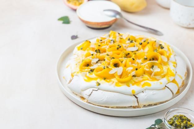 Tort bezowy pavlova ze świeżym mango i marakui oraz bitą śmietaną na tle łupkowym, kamiennym lub betonowym