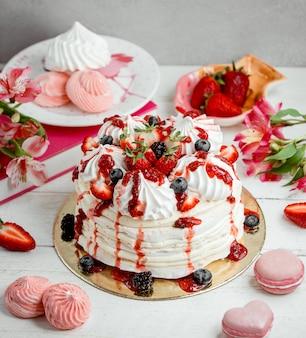 Tort bezowy z kremem i truskawką posypany syropem truskawkowym