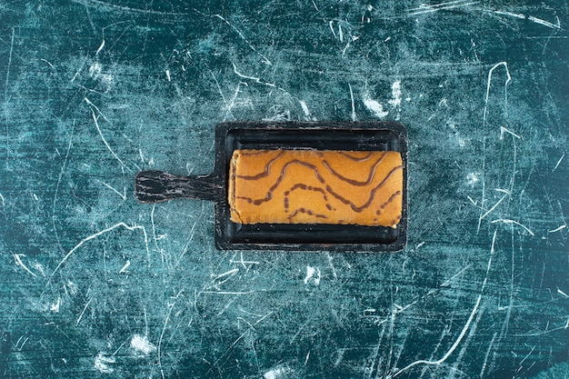 Tort bułka na desce, na niebieskim tle. zdjęcie wysokiej jakości
