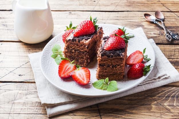 Tort czekoladowo-truflowy z truskawkami i miętą. drewniany stół.