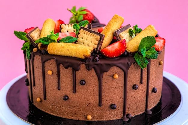 Tort czekoladowy hommade ozdobiony truskawkami na różowym tle