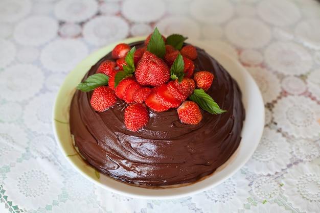 Tort czekoladowy ozdobiony truskawkami na białym talerzu