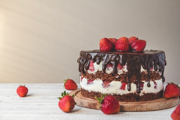 Tort czekoladowy z truskawkami na stole