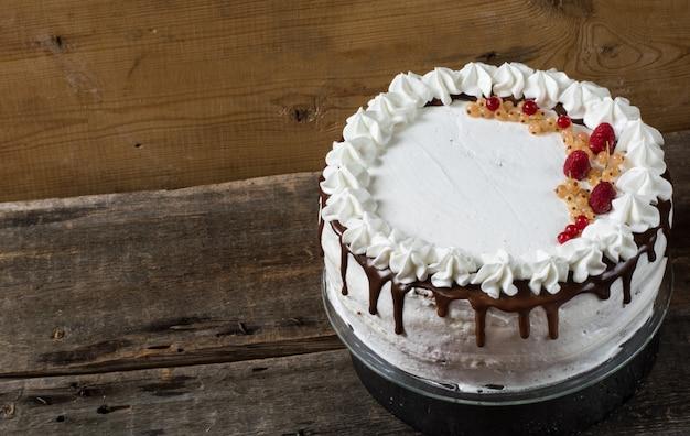 Tort kanapkowy victoria z truskawkami, żurawiną, miętą na stole. deser.