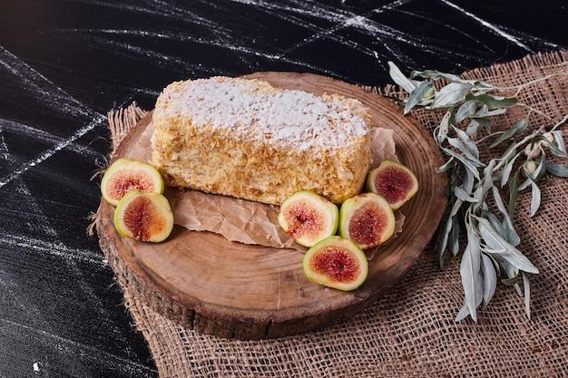 Tort napoelon z figami i liśćmi na wełnianym obrusie.