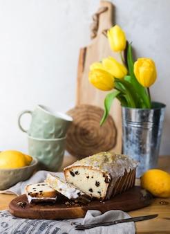 Tort rodzynkowy na drewnianej desce z cytryną i żółtymi tulipanami