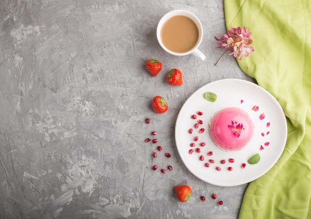 Tort różowy mus z truskawkami i filiżankę kawy na szarym tle betonu. widok z góry, kopia przestrzeń.
