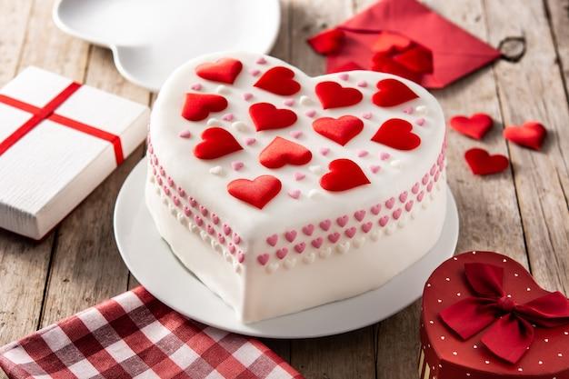 Tort serce na walentynki, dzień matki lub urodziny, ozdobione serduszkami z cukru na drewnianym stole