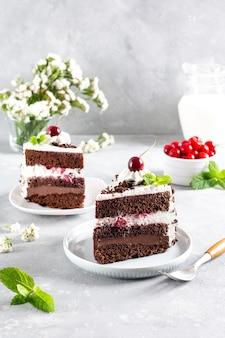 Tort szwarcwaldzki ozdobiony bitą śmietaną i wiśniami na jasnym betonowym stole, bułka z masłem. ciasto świąteczne